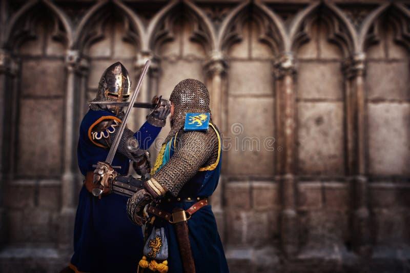 Due cavalieri che combattono la cattedrale medioevale di agaist immagine stock