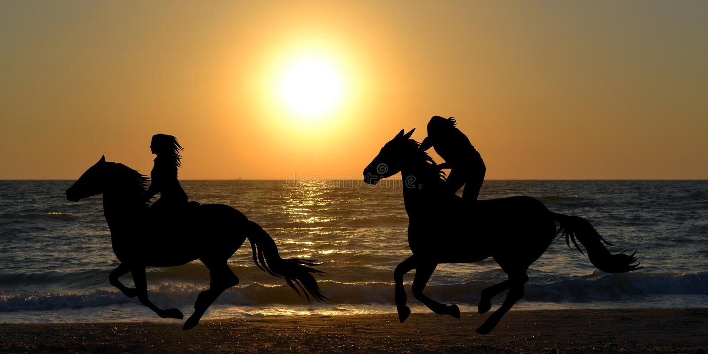 Due cavalieri del cavallo che galoppano sulla spiaggia fotografie stock libere da diritti