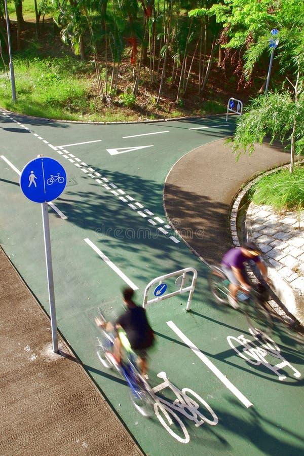 Due cavalieri della bicicletta che seguono i segnali stradali immagini stock