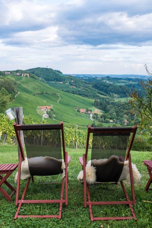 Due chaise-lounge con pelliccia per il rilassamento vicino alla vigna sulla Stiria del sud fotografia stock