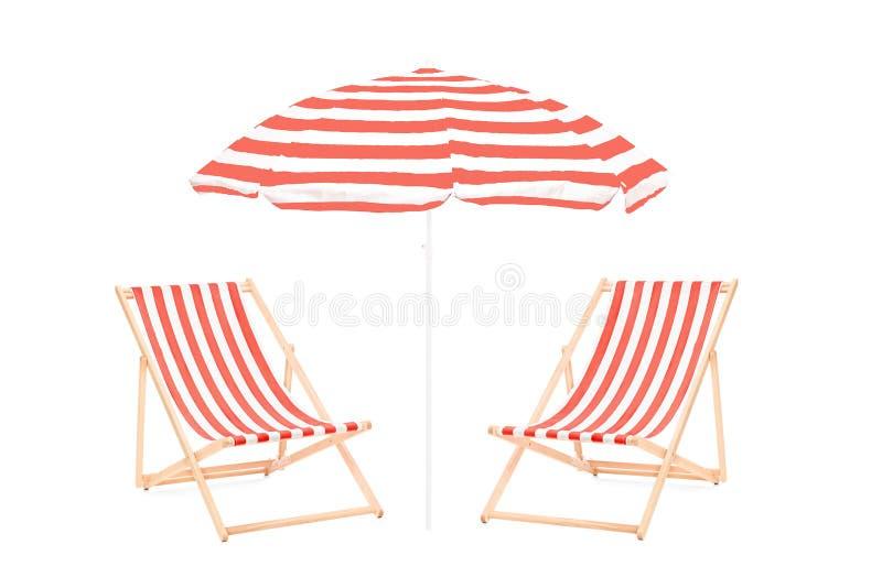 Due chaise-lounge del sole della spiaggia e un ombrello fotografia stock