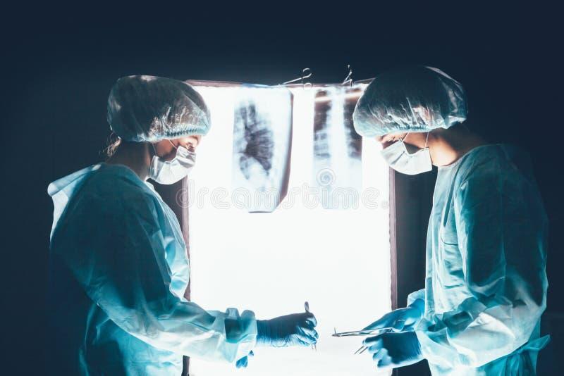 Due chirurghi che lavorano e che si concentrano al tavolo operatorio fotografia stock libera da diritti