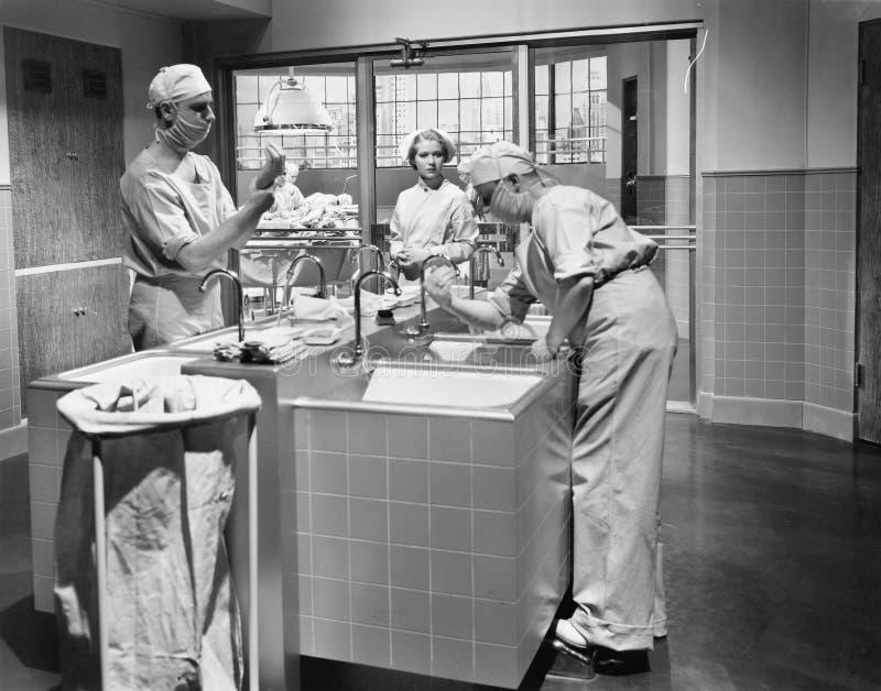 Due chirurghi e un infermiere nella stanza di sfregatura che prepara per un'operazione (tutte le persone rappresentate non sono v fotografia stock libera da diritti