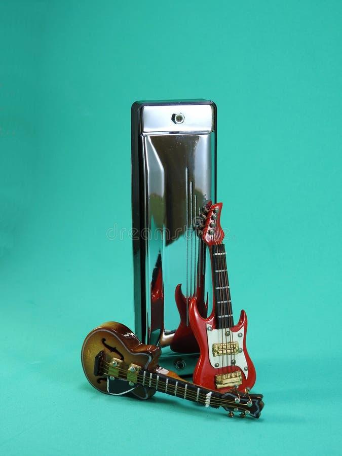 Due chitarre elettriche miniatura accanto ad un'armonica diatonica fotografie stock libere da diritti
