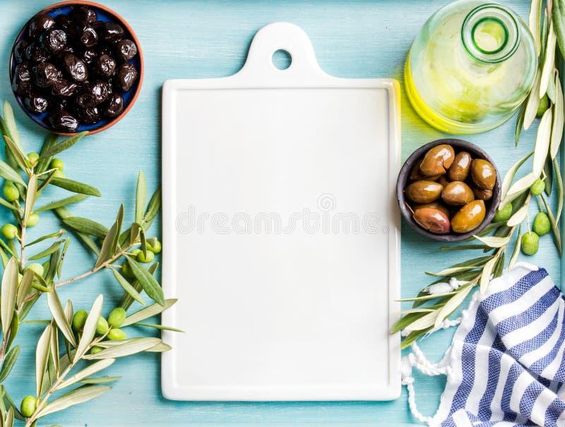Due ciotole con le olive verdi e nere marinate, ramoscelli di olivo, olio in bottiglia di vetro, bordo ceramico bianco nel centro immagini stock libere da diritti