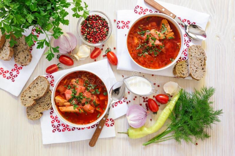 Due ciotole di borscht ucraino sui tovaglioli ricamati, pane, panna acida, spezie, cipolle, aglio, pomodori, prezzemolo fotografia stock libera da diritti