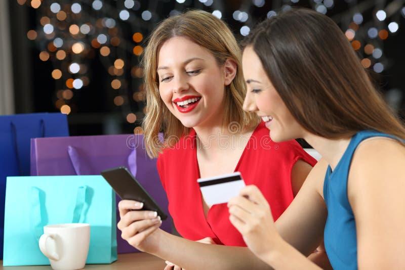 Due clienti che comperano sulla linea con la carta di credito immagine stock libera da diritti