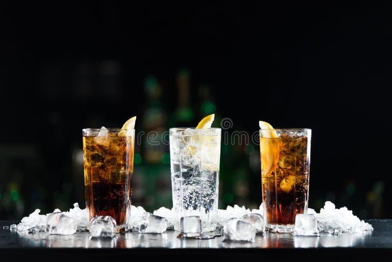 Due cocktail del coke e del whiskey ed una bevanda alcolica bianca sulla tavola della barra fotografia stock libera da diritti