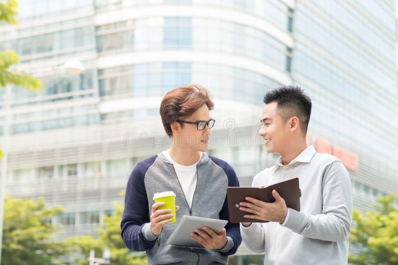 Due colleghe maschii sorridenti del lavoro all'aperto che parlano insieme sopra la a immagini stock