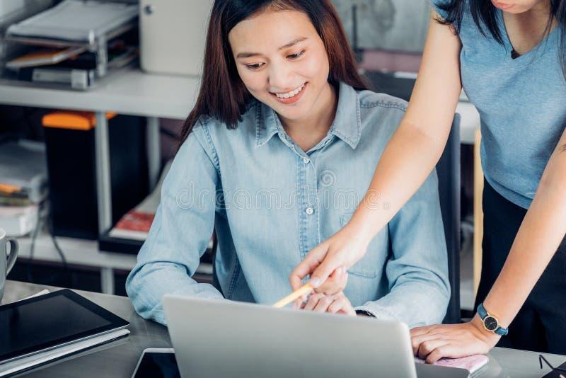 Due colleghi asiatici della donna causali incontrando a casa ufficio discus immagini stock