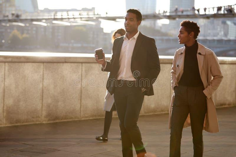 Due colleghi che camminano dalla riva del fiume di Tamigi nella città di Londra che parla, uomo di affari che tiene caffè asporta immagine stock libera da diritti
