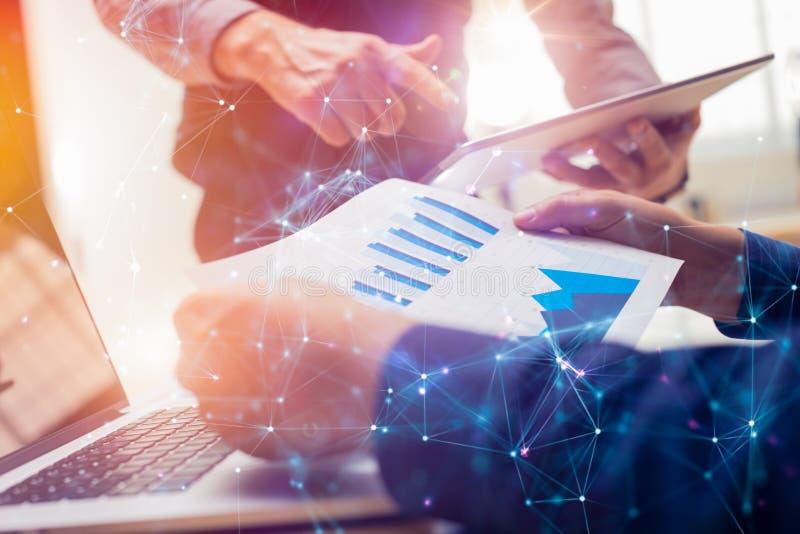 Due colleghi che lavorano alla nuova strategia finanziaria globale progettano per mezzo della compressa e del computer portatile  immagine stock