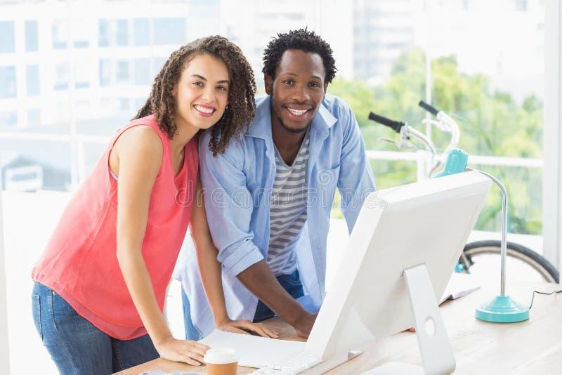 Due colleghi creativi di affari che discutono sopra un computer fotografia stock