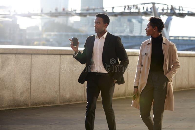 Due colleghi di affari che camminano dalla riva del fiume di Tamigi nella città di Londra che parla, gesturing dell'uomo fotografia stock libera da diritti