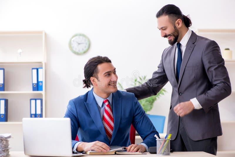 Due colleghi maschii nell'ufficio fotografie stock libere da diritti