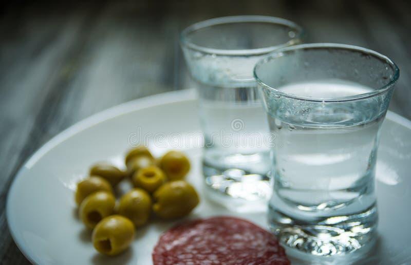 Due colpi di vodka, di olive e delle fette del salame sul piatto bianco, primo piano immagine stock