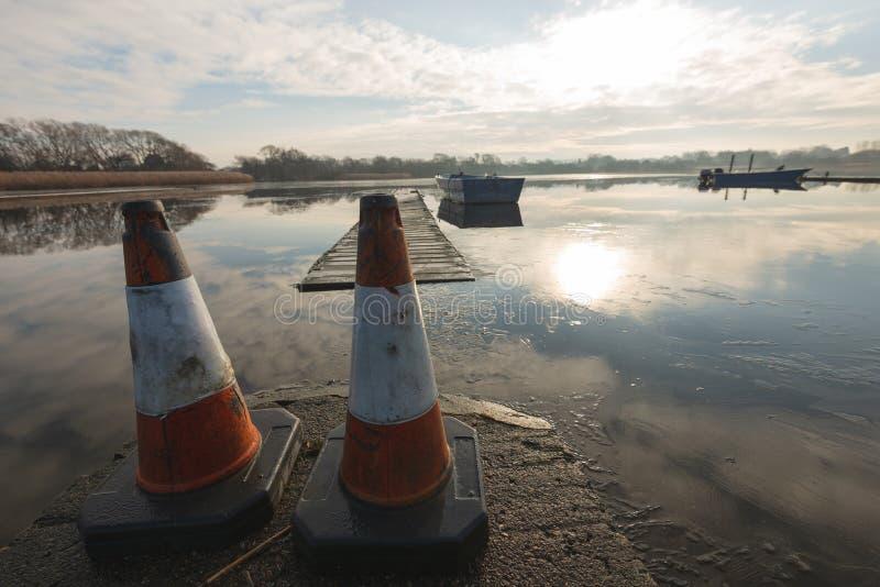 Due coni di traffico si siedono su un passaggio pedonale che impedisce la gente che va vicino ad un lago congelato fotografia stock libera da diritti
