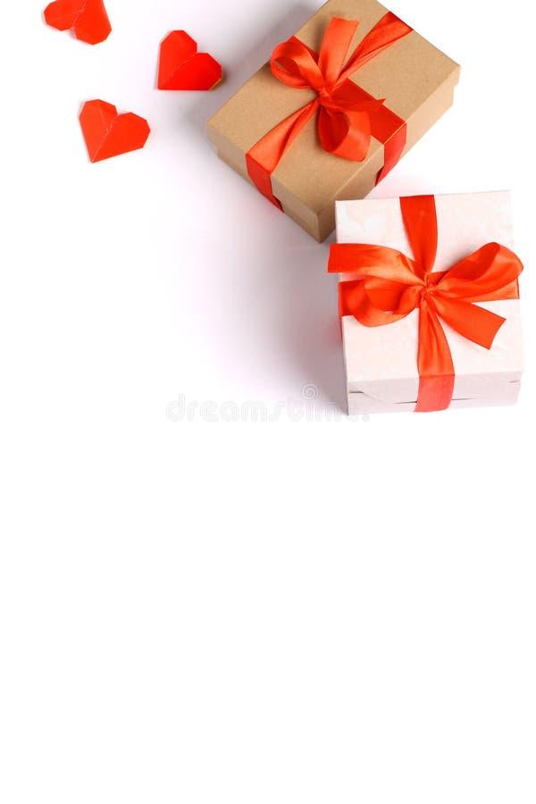 Due contenitori di regalo del cartone con un arco rosso del nastro hanno isolato fotografie stock