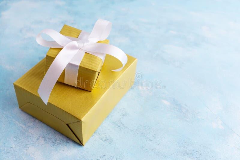 Due contenitori di regalo in oro incartano l'arco bianco del witn su fondo blu Concetto di festa Nuovo anno, Natale, compleanno immagini stock