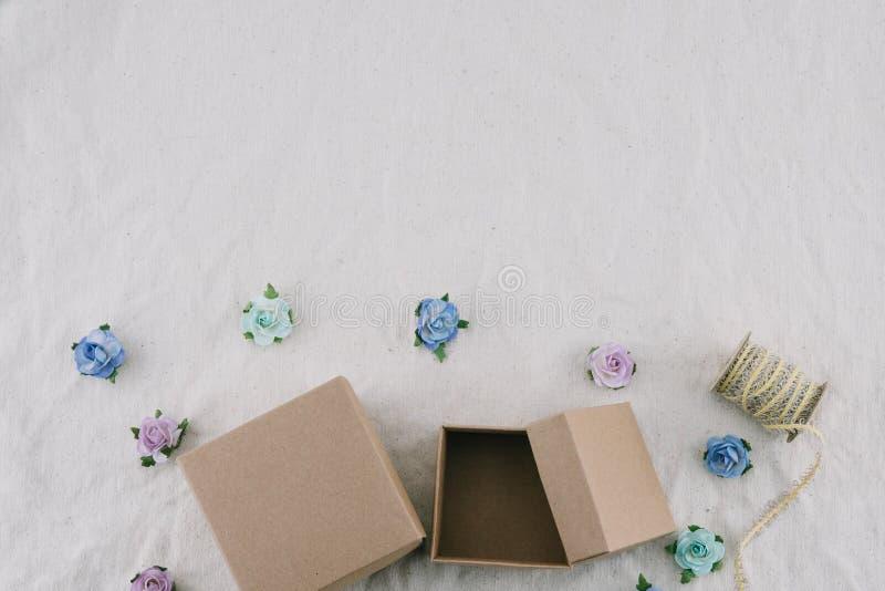 Due contenitori e corde di regalo marroni decorano con i fiori di carta del tono blu fotografia stock