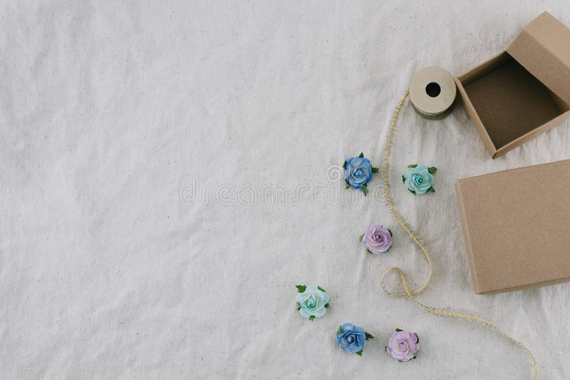 Due contenitori e corde di regalo marroni decorano con i fiori di carta del tono blu immagine stock libera da diritti