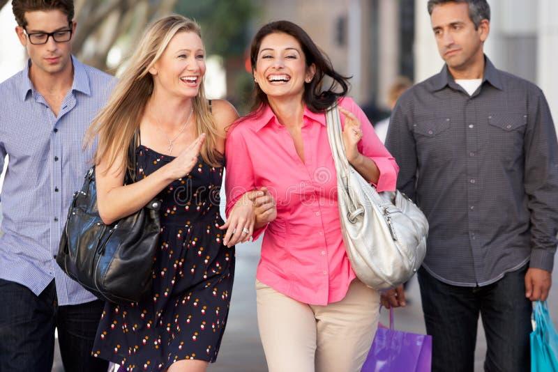 Due coppie con gli uomini annoiati che portano le borse dei partner fotografia stock libera da diritti