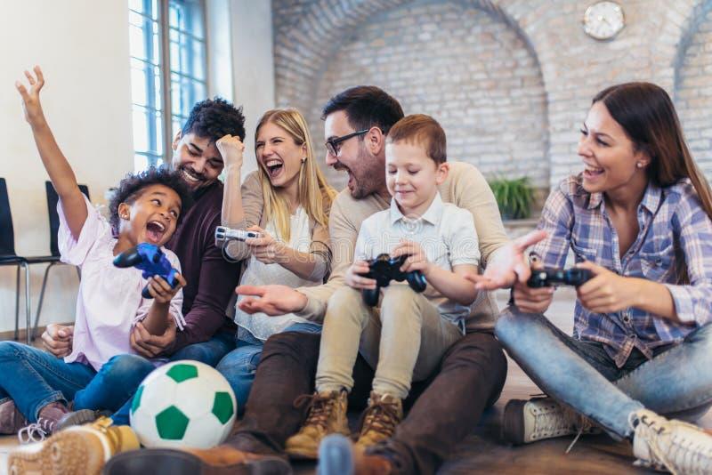 Due coppie della corsa mista giocano i video giochi con i loro bambini fotografie stock libere da diritti