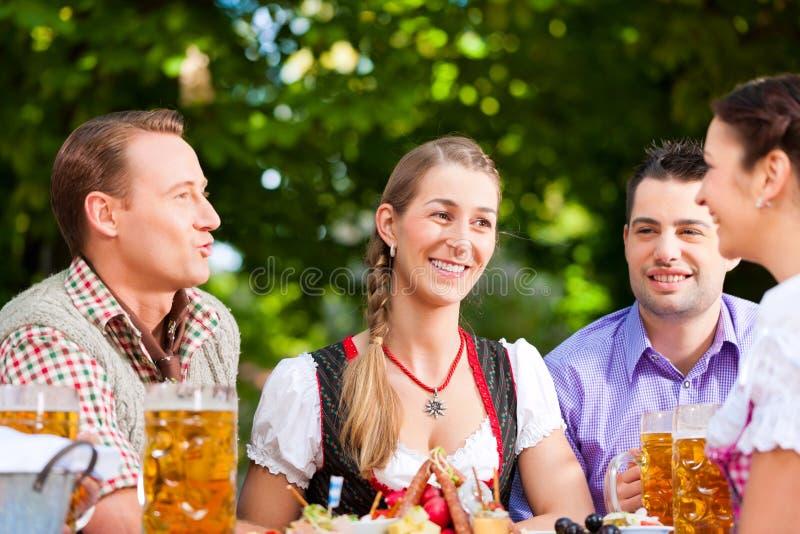 Due coppie felici che si siedono nel giardino della birra fotografie stock