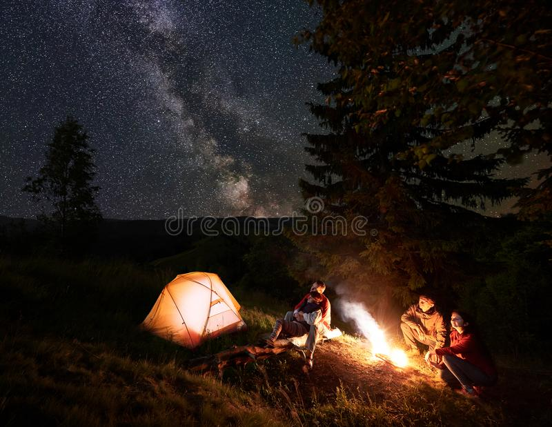 Due coppie si avvicinano al fuoco di accampamento alla notte nel legno che gode del cielo stellato fotografie stock