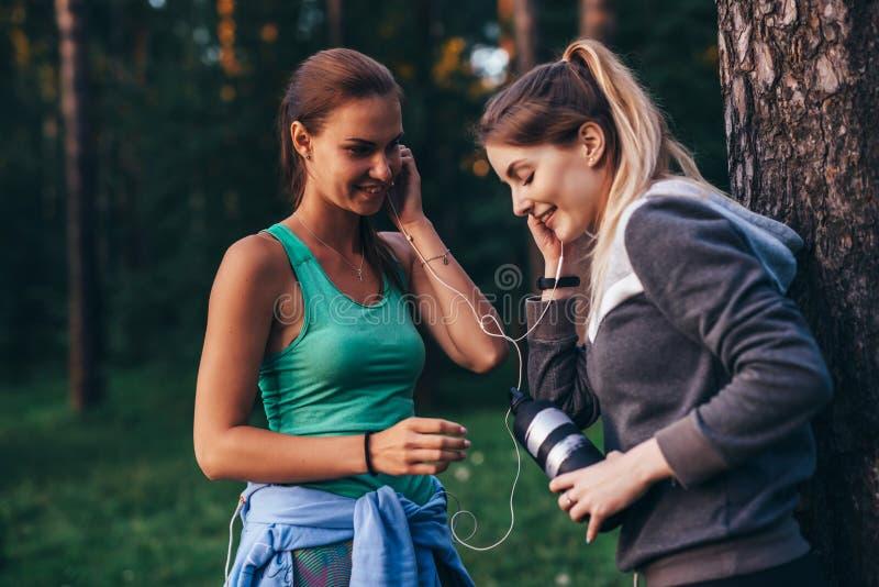 Due corridori femminili che si rilassano dopo l'allenamento che sta vicino all'albero che parla nel parco immagini stock