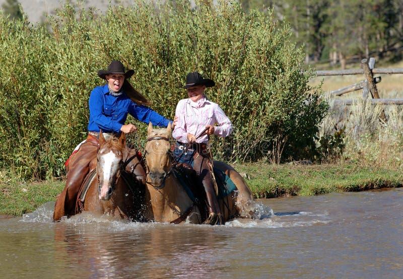 Due Cowgirls che entrano in stagno fotografie stock