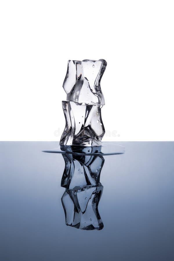 Due cubetti di ghiaccio con le gocce di acqua isolate su bianco e su blu fotografie stock libere da diritti