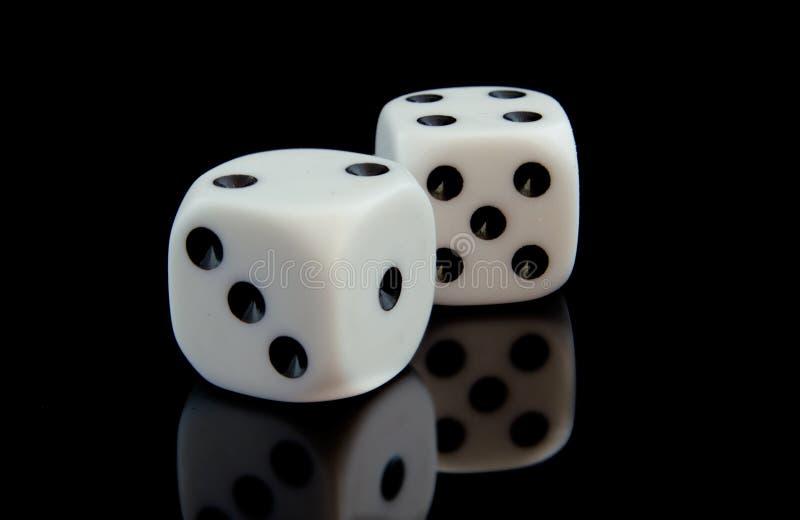Due cubi del gioco sulla superficie riflettente nera immagini stock libere da diritti