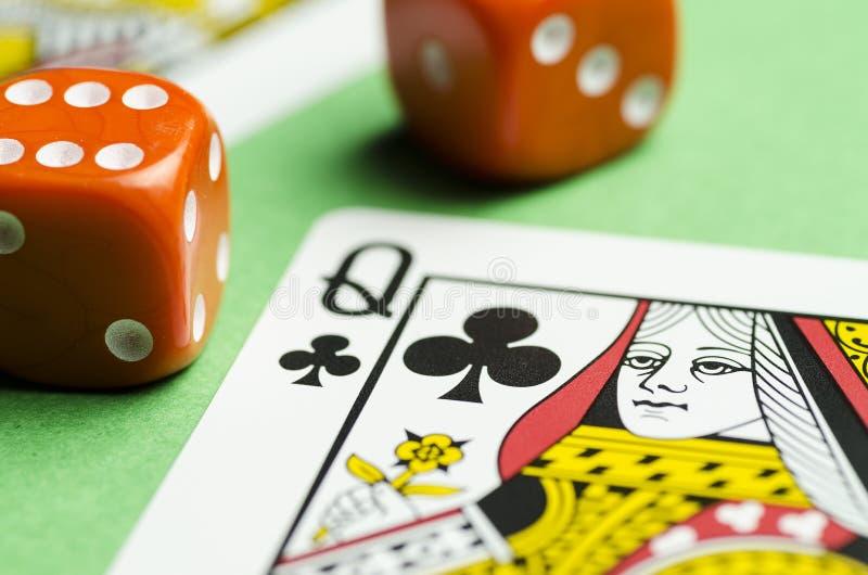 Due cubi rossi e una carta da gioco della regina su un fondo verde fotografia stock libera da diritti