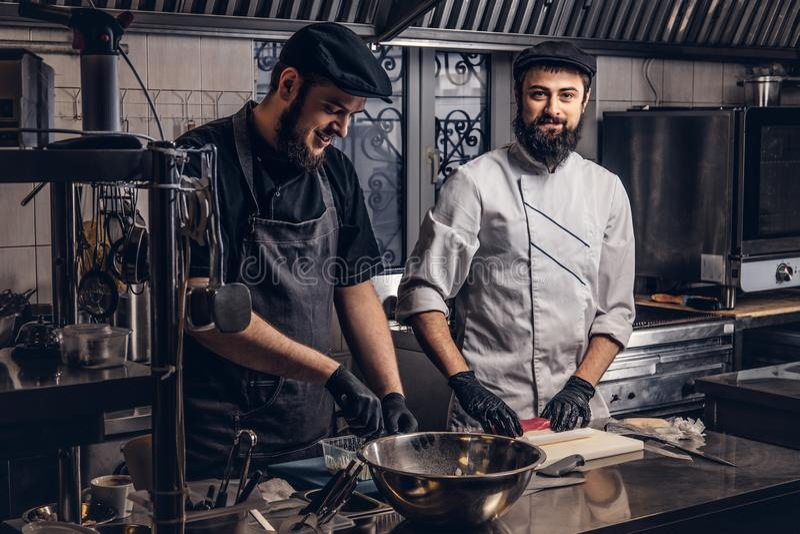 Due cuochi barbuti sorridenti si sono vestiti in uniformi che preparano i sushi nella cucina immagine stock