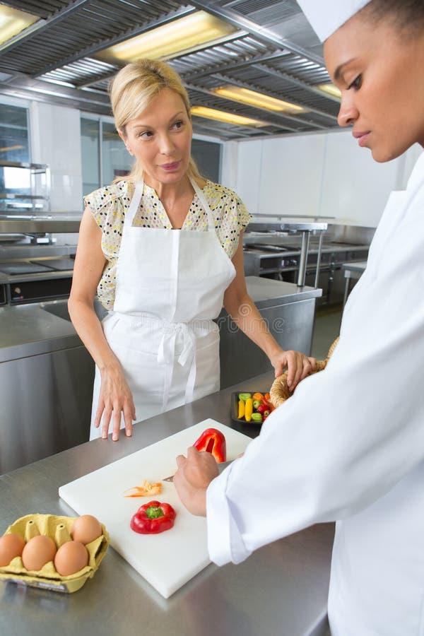 Due cuochi unici femminili che lavorano accanto ad a vicenda nella cucina dell'hotel immagine stock