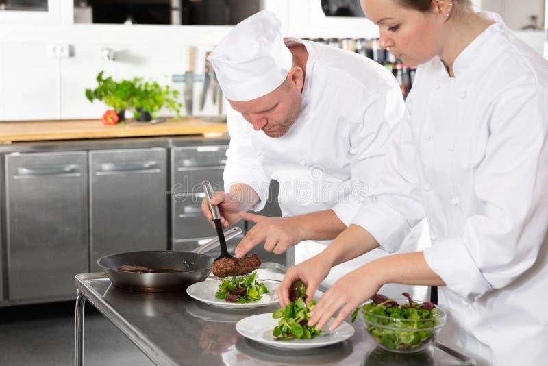 Due cuochi unici professionisti prepara il piatto della bistecca al ristorante gastronomico fotografia stock
