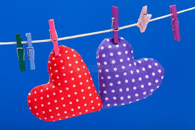 Due cuori che appendono su un clothesline con i clothespins immagini stock libere da diritti