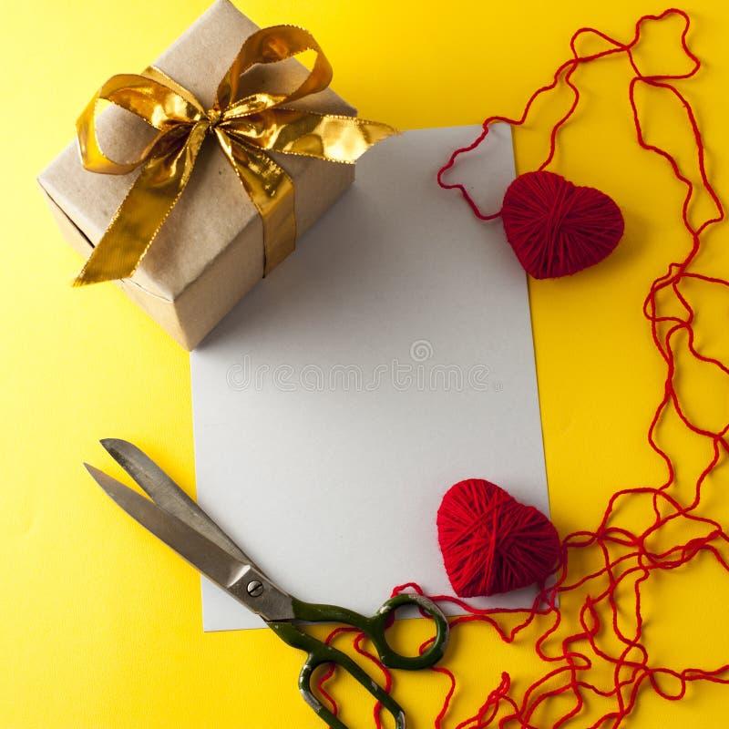 Due cuori, contenitore di regalo e forbici tricottati fotografia stock