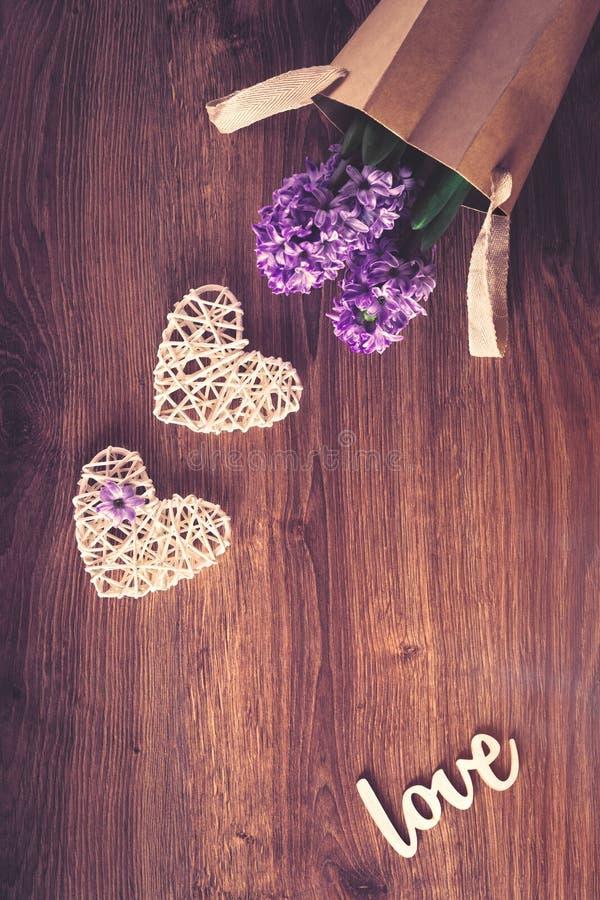 Due cuori del sisal e fiori del hiacinth in una borsa fotografie stock