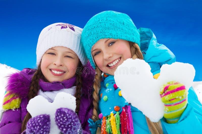 Due cuori della neve della tenuta del ritratto delle ragazze fotografia stock
