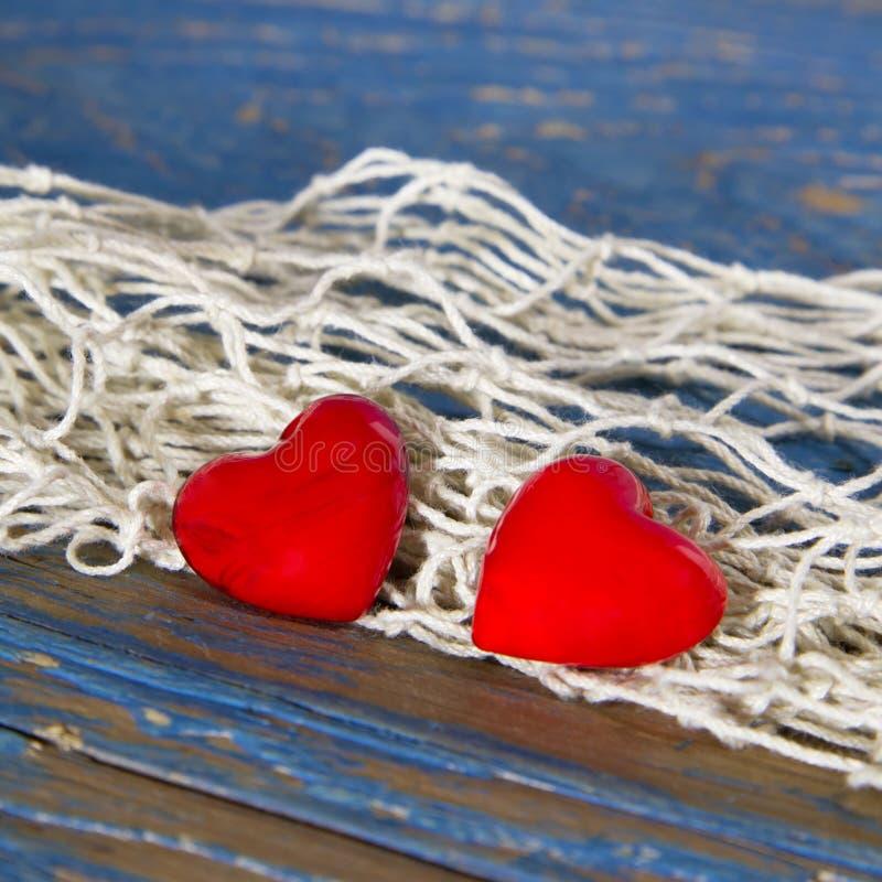 Due cuori e corde rossi su superficie di legno blu. fotografie stock libere da diritti