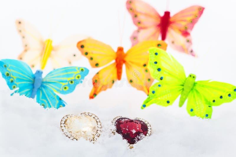 Due cuori e farfalle decorativi nella neve fotografie stock libere da diritti