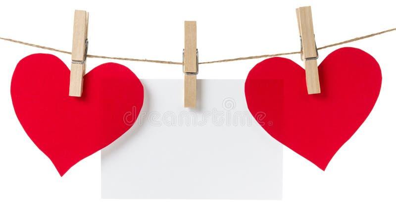 Due cuori ed attaccature di carta rossi della scheda fotografie stock