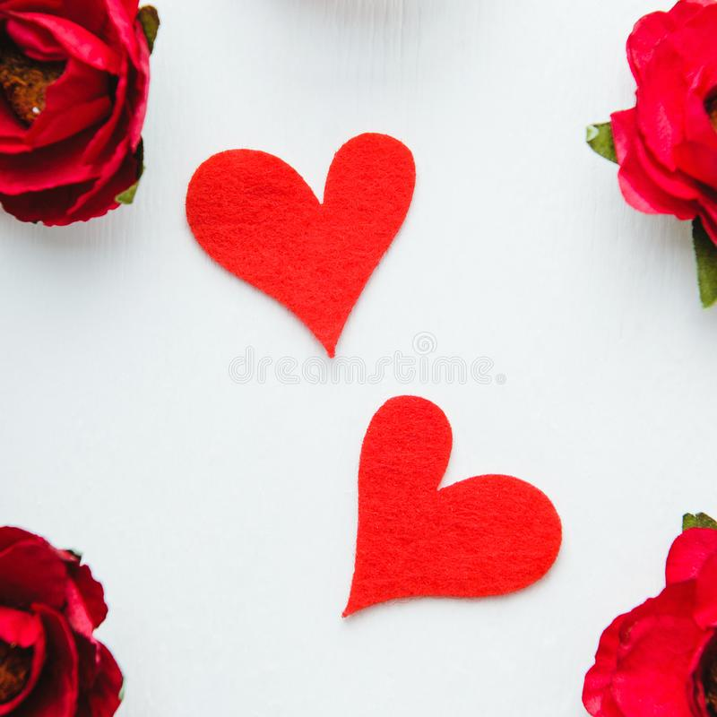 Due cuori ritenuti rossi su fondo bianco con i fiori di carta rossi Giorno del ` s del biglietto di S. Valentino, amore Vista sup fotografia stock