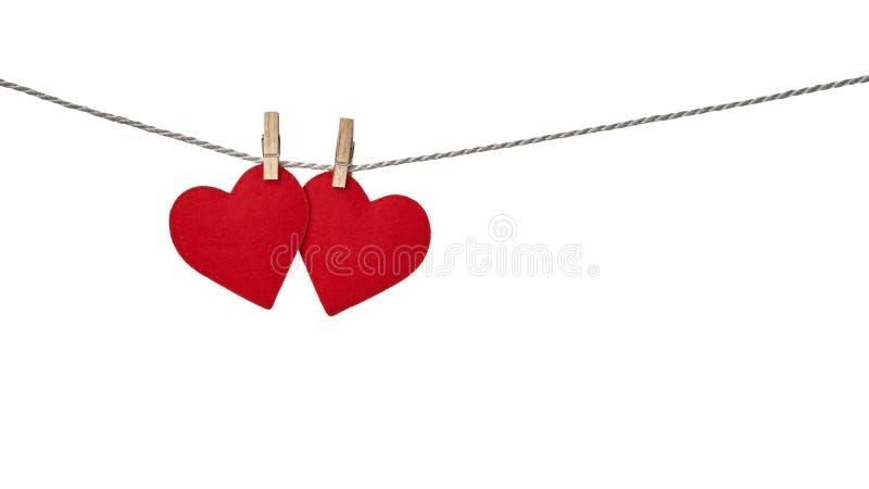 Due cuori rossi del biglietto di S. Valentino che pendono da una corda riparata dalle mollette da bucato isolate su fondo bianco immagine stock