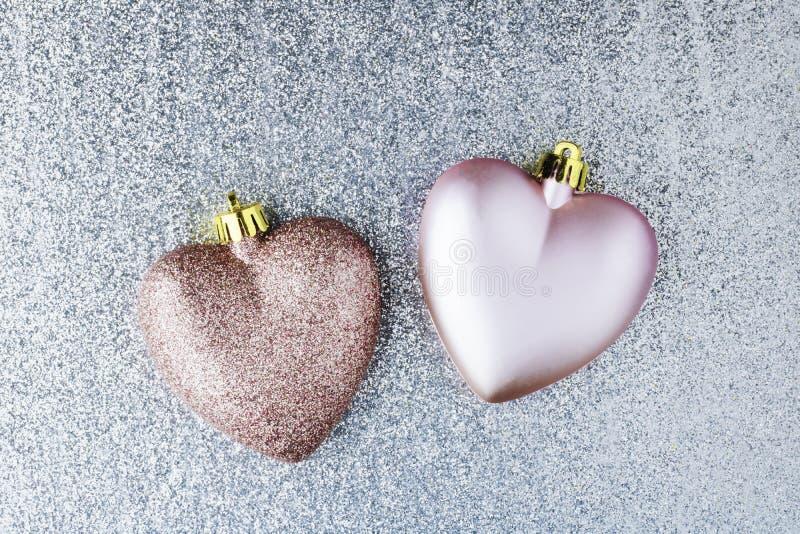 Due cuori su fondo d'argento Decorazioni per l'albero di Natale Concetto natale, amore, giorno di San Valentino Glare fotografia stock libera da diritti