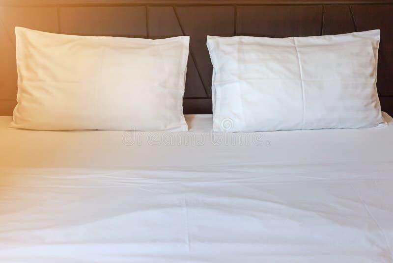 Due cuscini bianchi con lo strato bianco della lettiera sul letto vuoto in camera da letto fotografia stock libera da diritti