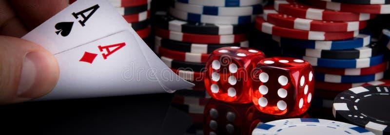 Due dadi e carte rossi di gioco sui precedenti delle pile di chip di poker fotografia stock