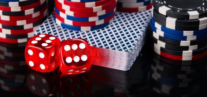 Due dadi rossi, una piattaforma delle carte e chip di mazza, su un fondo nero fotografia stock libera da diritti